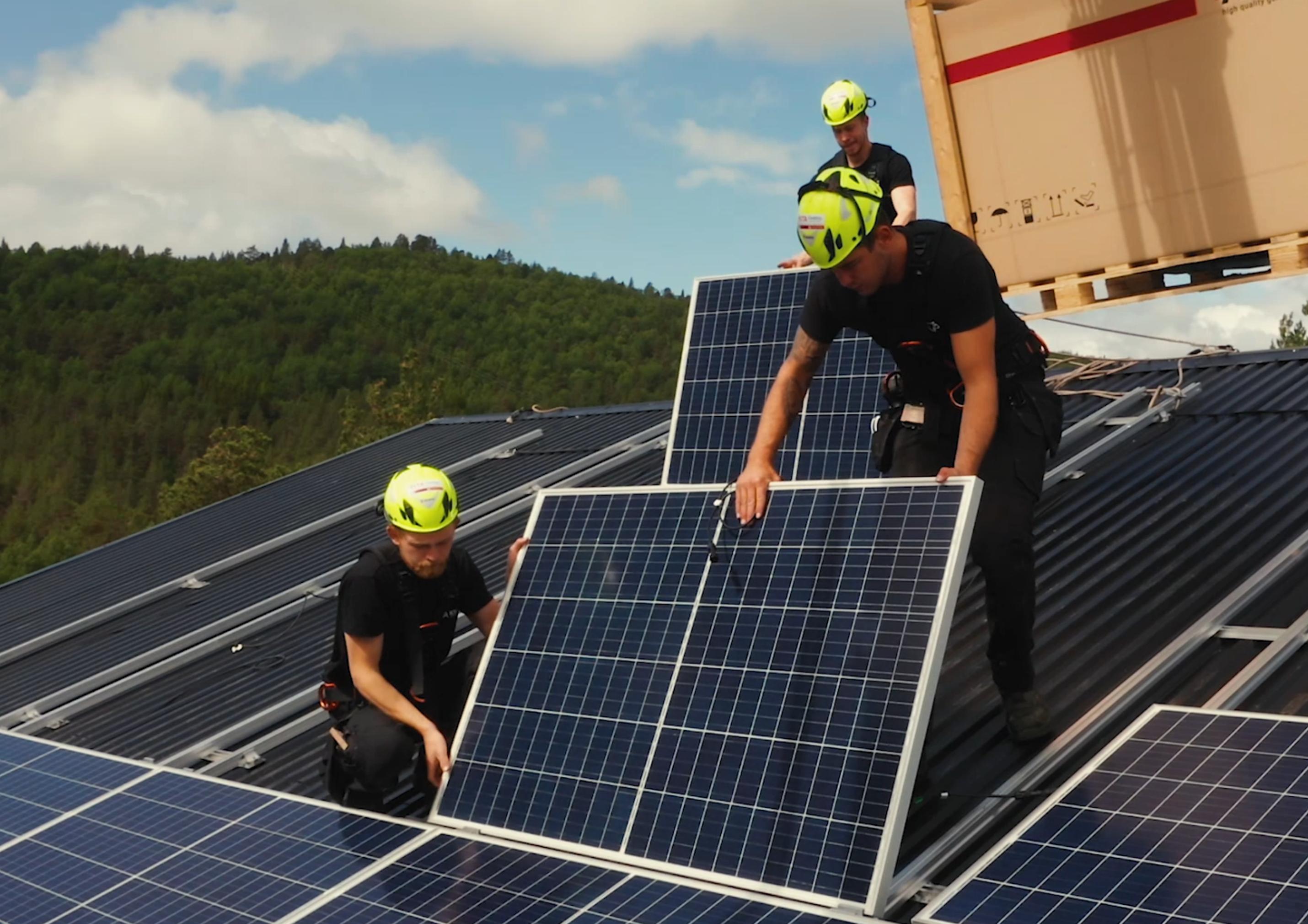 Tre montører monterer solcelleanlegg på et tak.