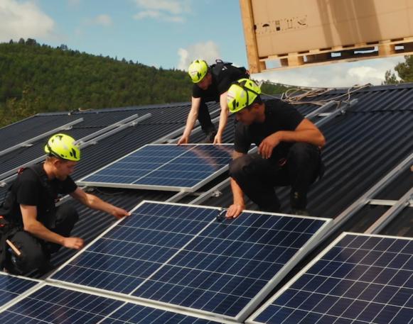 Tre montører fra EnergiPluss som monterer solcelleanlegg på et tak