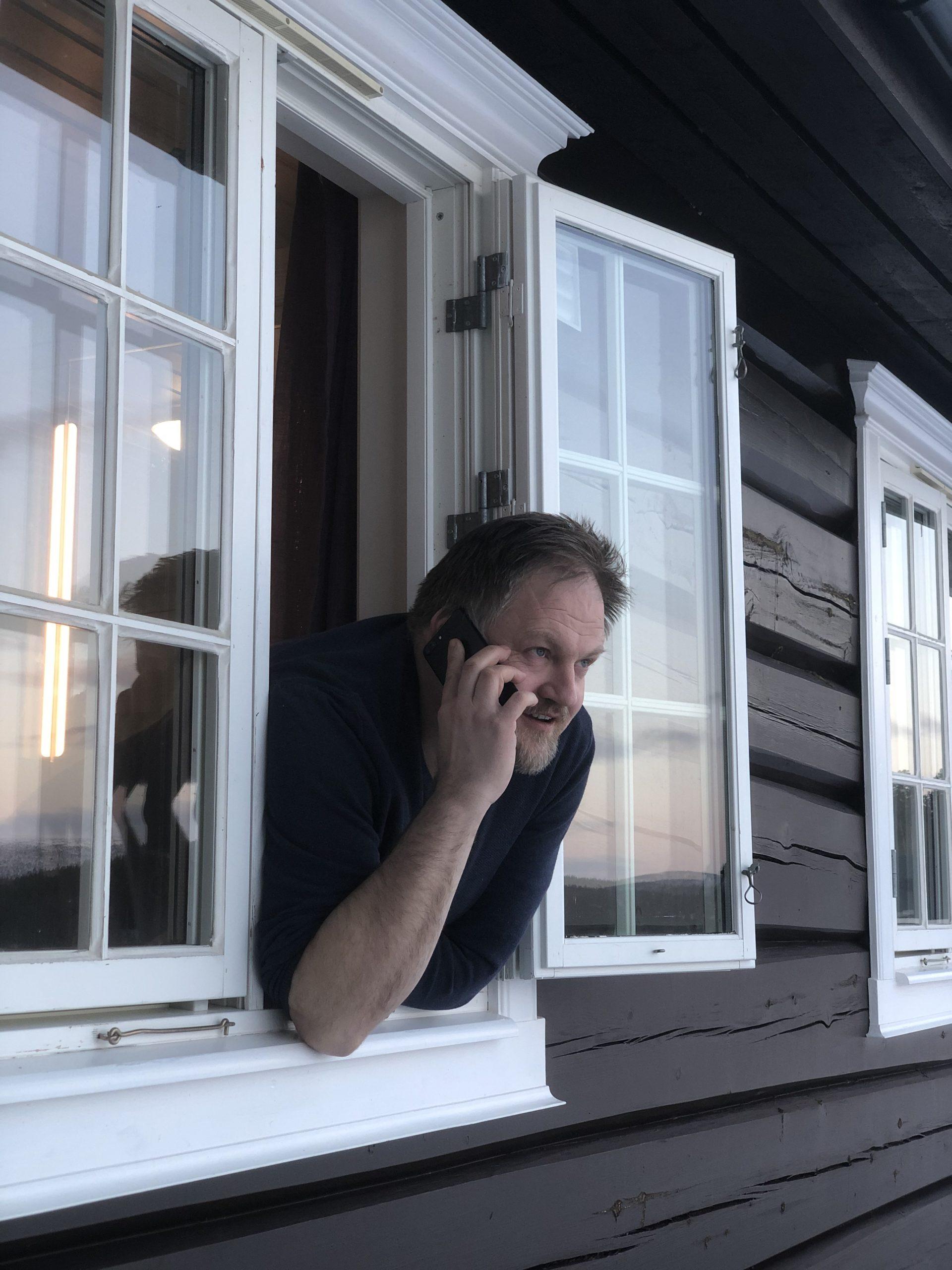 Rådmann Erling Strålberg henger ut av et vindu med telefonen til øret.