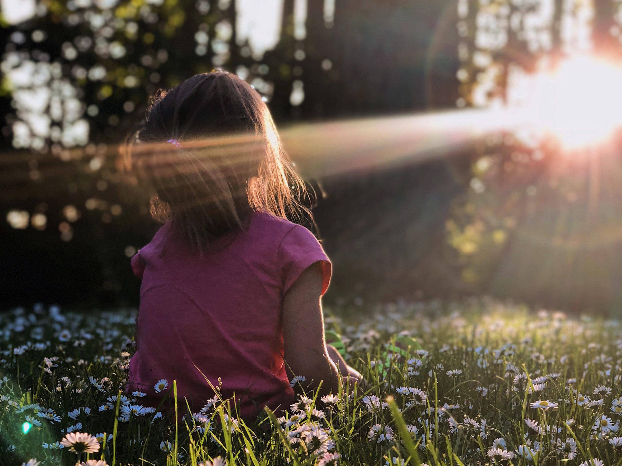 jente i gress ser på solen